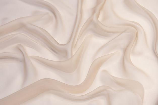 Абстрактная предпосылка текстуры ткани шелкового шифона цвета шампанского.