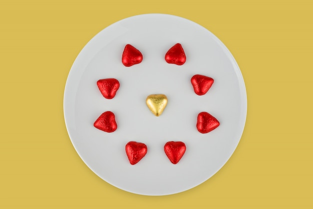 Абстрактные шоколадные конфеты в форме сердца на белой тарелке