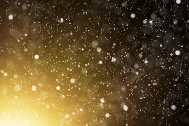 디자인 또는 모형을 위한 밝은 빛에 흐릿한 눈송이가 있는 추상 크리스마스 배경