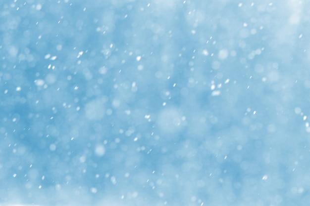 Абстрактный новогодний фон со снежинками во время снегопада на размытом фоне