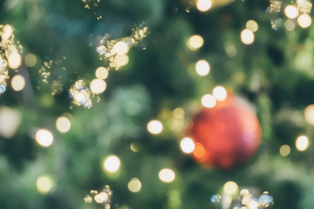 木のぼやけた背景にお祝いの金のボケ光と抽象的なクリスマス休暇
