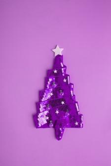 반짝이는 리본으로 만든 추상 크리스마스 트리에는 새해 홀을 위한 최소한의 크리에이티브가 있는 스팽글이 있습니다.