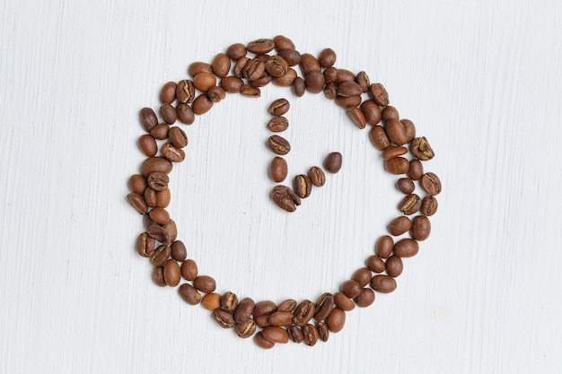 Abstract clock of coffee beans on a white background.