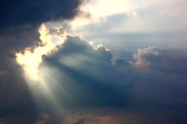 太陽の光が空の背景を通過する抽象的な雲の形