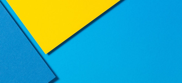 Abstract color papers geometry flat lay composition banner background with yellow and blue tones