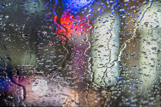 Abstract colorful background of glass surface with water drops and blurred city lights