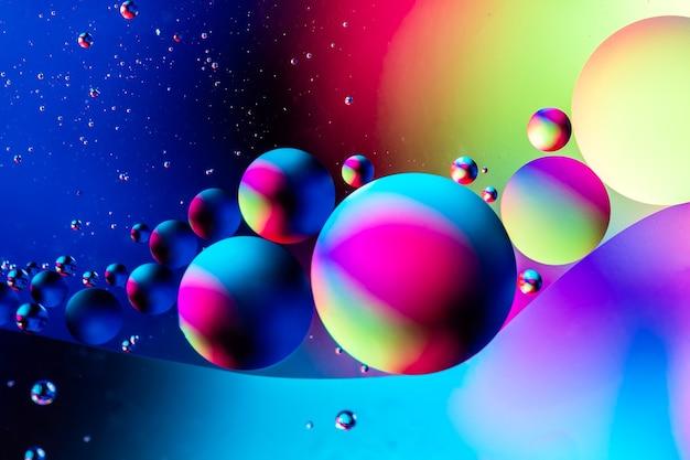 水面に油と抽象的なカラフルな背景。水に油滴がサイケデリックを抽象化します。宇宙と宇宙の惑星は、サイケデリックな抽象的なイメージをスタイルしました。