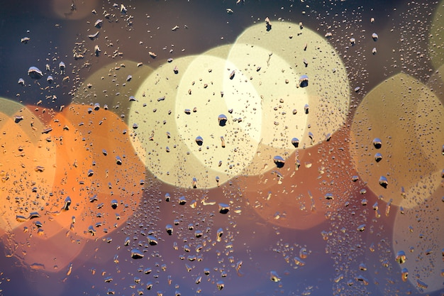 Abstract colorful bokeh background with yellow circles and water drops on glass surface in front. blurred city lights.