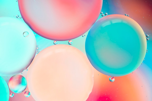 Abstract colorful bubbles in water on hued blurred background
