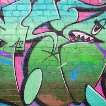 Abstract colorful fragment of graffiti paintings on old brick wall in pink and green colors