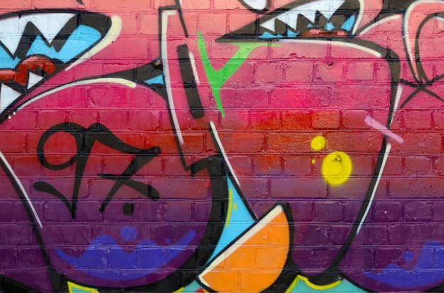 Abstract colorful fragment of graffiti paintings on old brick wall