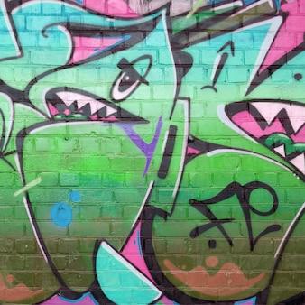 녹색 색상의 오래 된 벽돌 벽에 낙서 그림의 추상 화려한 조각