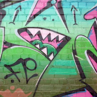 Абстрактный красочный фрагмент граффити на старой кирпичной стене в розовых и зеленых тонах