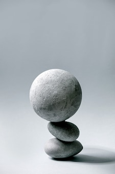 Abstract  composition of balanced grey geometric objects sphere and stones. copy space. modern concept for product presentation.