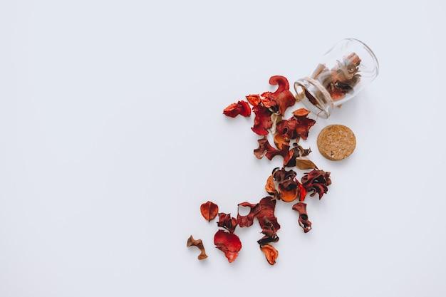 Абстрактная композиция. стеклянная банка с рассыпанными красными засушенными лепестками на белом фоне