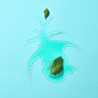 Abstract composition of melted ice cream on a blue glass background with mint leaves clear boundaries and reflection. top view
