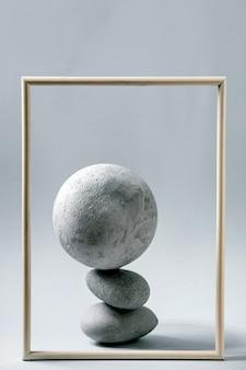 バランスの取れた灰色の幾何学的なオブジェクトの球、額縁、石の抽象的な構成。コピースペース。製品プレゼンテーションのモダンなコンセプト。