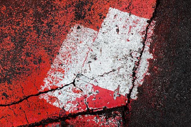 アスファルトの抽象的な構成。アスファルトの背景に抽象的なサイン。斑点のあるアスファルト道路のテクスチャと古いひびの入ったアスファルト表面のパターンがクローズアップ