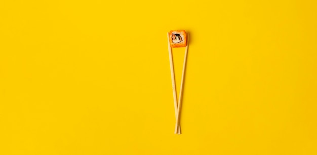 An abstract concept of the asian wooden chopsticks with a roll national food on color surface , wide banner