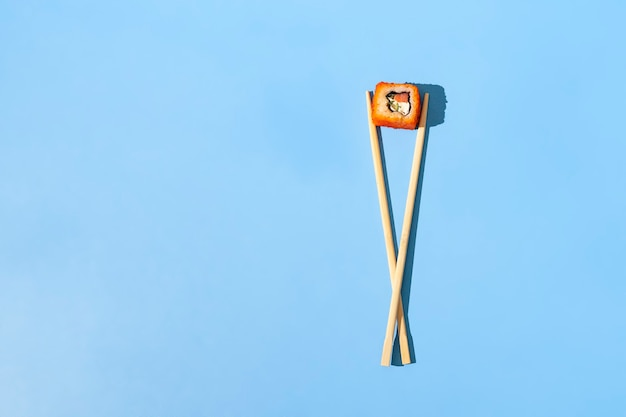 An abstract concept of the asian wooden chopsticks with a roll national food on color surface