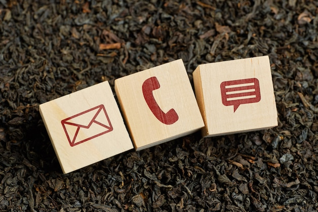 Abstract contact icons - envelope, phone, message - on wooden cubes and dry tea.
