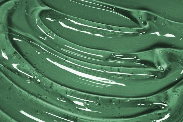 Абстрактный косметический фон из прозрачного геля или антисептического гиалурона на зеленом фоне