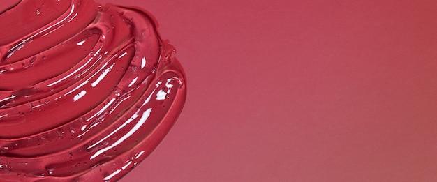 Абстрактный косметический фон из прозрачного геля или антисептического гиалурона на красном фоне с копией ...