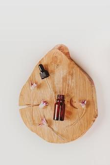 木製の表彰台の自然化粧品フラットセントに濃い琥珀色のガラスの抽象的な化粧品実験室ボトル...
