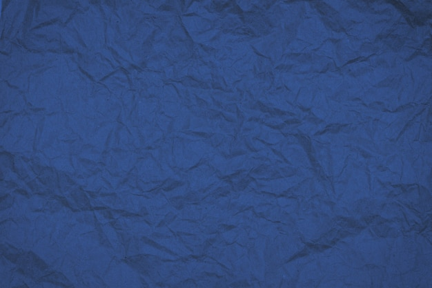 Abstract crumbled textured wrinkled paper toned in trendy 2020 classic blue, background.