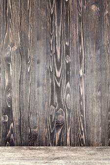 Абстрактная темная старая деревянная поверхность, изношенная со временем, которая разрушается на открытом воздухе из-за природных явлений, деталей и структуры дерева