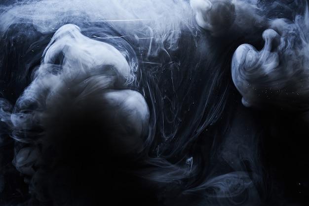 Абстрактная темная краска в водной предпосылке. движение облака белого дыма на черном, акриловые чернила вихревые брызги