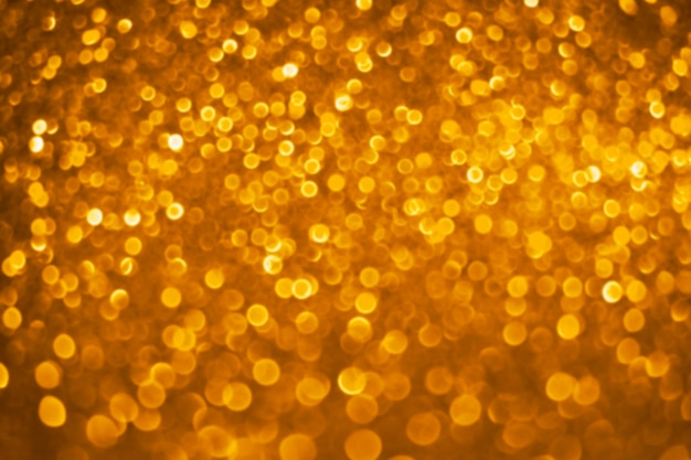 Abstract defocused golden bokeh background. christmas bokeh lights. festive glittering blurred texture