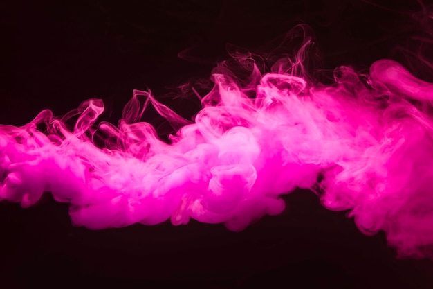 Abstract dense fluffy puffs of pink smoke on black background