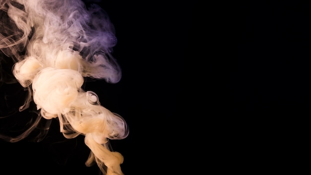 Abstract dense fluffy puffs of white smoke on black background with copy space