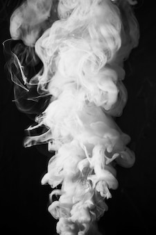 Abstract dense fluffy puffs of white smoke on black background