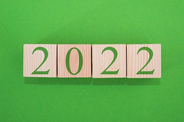 抽象的なデザインコンセプト-2022。緑の背景に立方体の新年の目標計画をクローズアップ、上面図。