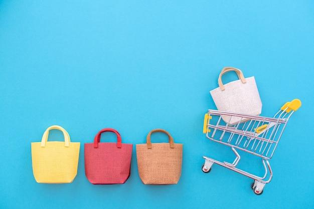 추상적인 디자인 요소, 연간 판매, 쇼핑 시즌 개념, 파스텔 파란색 배경에 화려한 종이 가방이 있는 미니 노란색 카트, 위쪽 전망, 평평한 평지