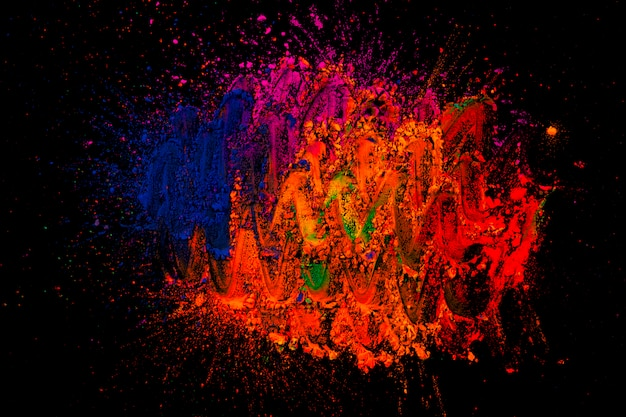 Abstract design on rangoli colors over dark surface