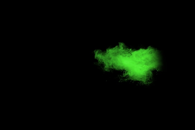 Abstract dust explosion frozen green on black background.