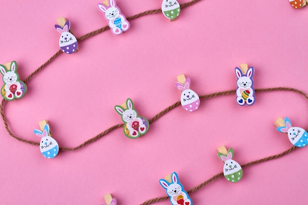 Abstract easter composition. brown thread and decorative easter rabbits on pink background.