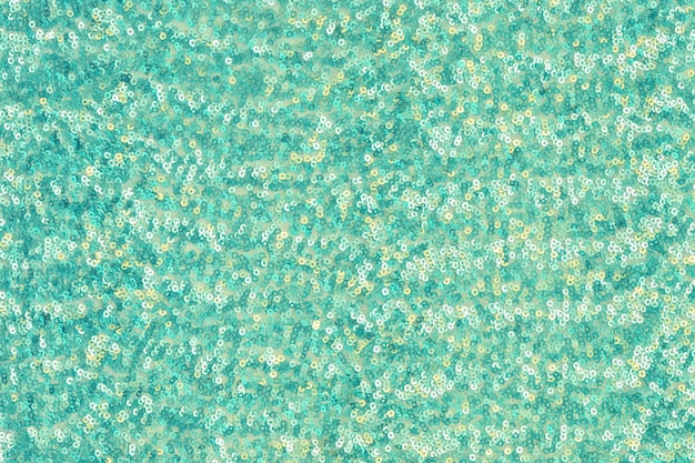 Abstract festive background with round sequins with color transition. mint color.