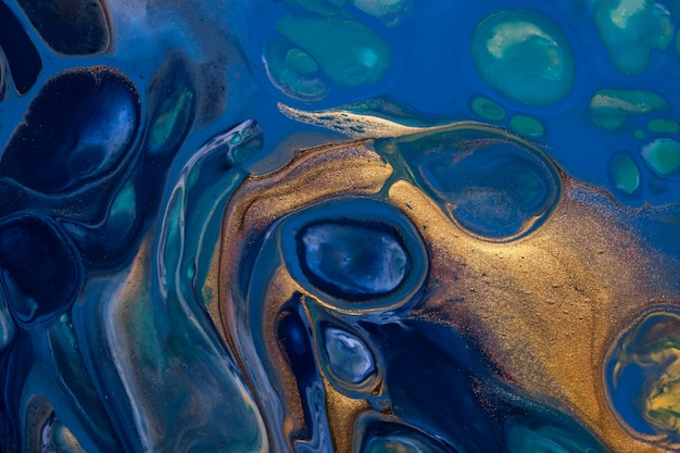 Abstract fluid art background blue and golden colors. liquid acrylic painting on canvas with gradient. watercolor backdrop with  pattern.