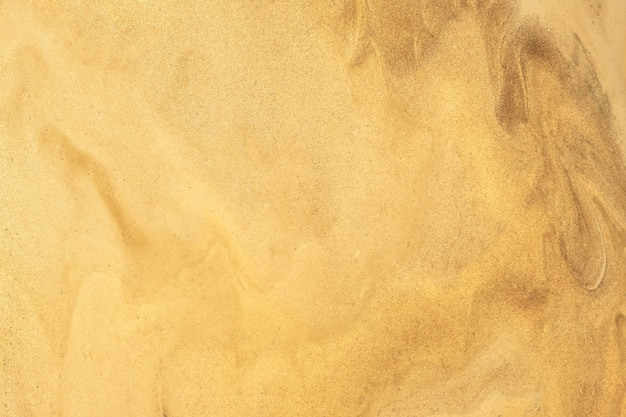 Abstract fluid art background dark golden colors. liquid marble. acrylic painting on canvas with yellow shiny gradient. alcohol ink backdrop with pearl wavy pattern.