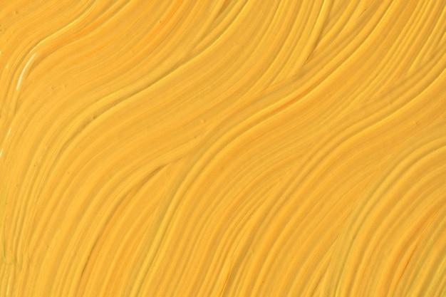 抽象的な流体アートの背景の濃い黄色。液体大理石。金色のグラデーションでキャンバスにアクリル画。波状のパターンの水彩画の背景。