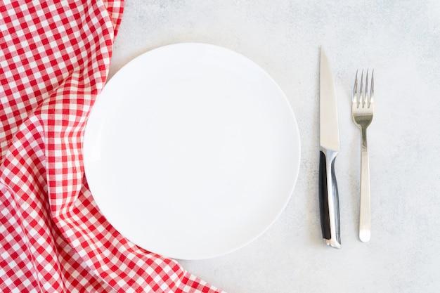 赤と白のナプキンとカトラリーと抽象的な食品背景空の白いプレート