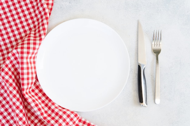Abstract food background empty white plate with red and white napkin and cutlery