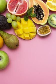 食品の背景を抽象化、コピースペースを持つ果物フレーム。ピンクの背景。
