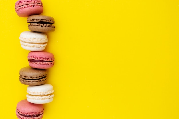 Abstract food background with macaroons cakes on yellow background.