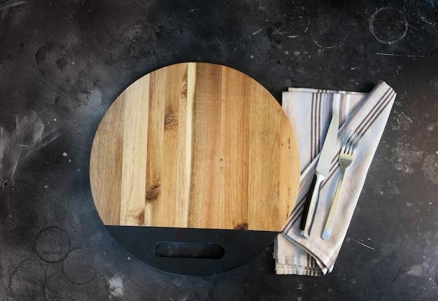 台所のテーブルの上にカトラリーと抽象的な食品の背景木製の空のボード