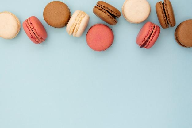 青い背景上のおいしいマカロンと抽象的な食品写真の背景。